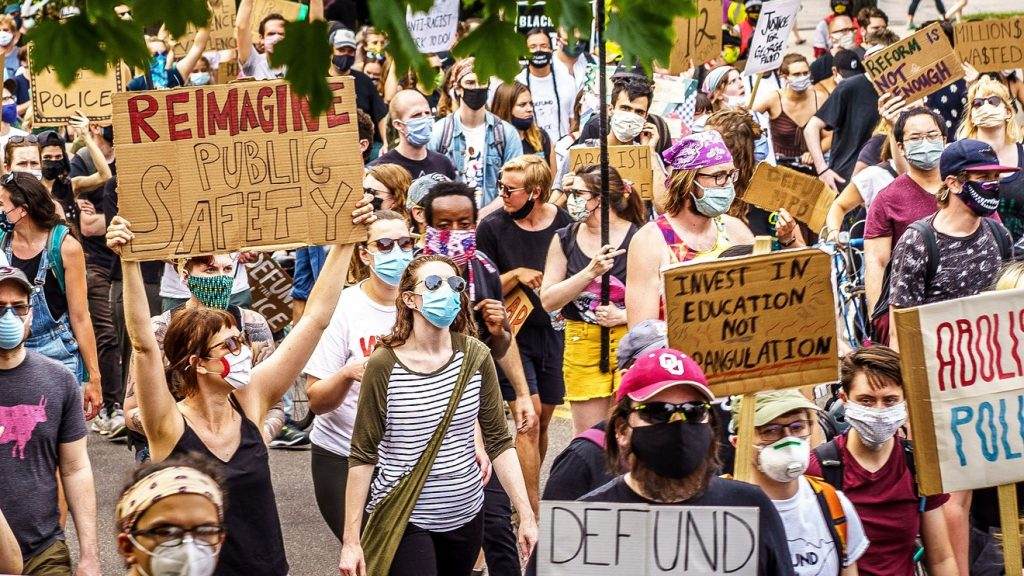 """Demonstrators in Minneapolis ask us to """"Reimagine Public Safety"""" and to """"Invest in Education — Not Strangulation"""" as well as to """"Defund the Police."""" AFP VIA GETTY IMAGES"""